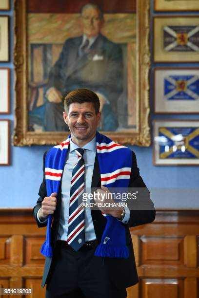 Former England and Liverpool captain Steven Gerrard smiles as he poses for a photograph with a Rangers scarf in front of the portrait of former...