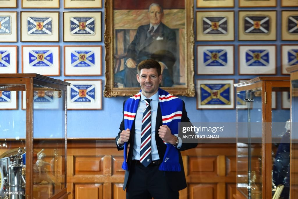 Former England and Liverpool captain Steven Gerrard smiles as he poses for a photograph with a Rangers scarf, in front of the portrait of former manager Bill Struth in the trophy room as he is unveiled as Rangers' new manager at Ibrox Stadium in Glasgow, Scotland on May 4, 2018. - Rangers on Friday confirmed former Liverpool and England midfielder Steven Gerrard as their new manager, announcing he would join the Scottish Premiership club this summer on a four-year deal.