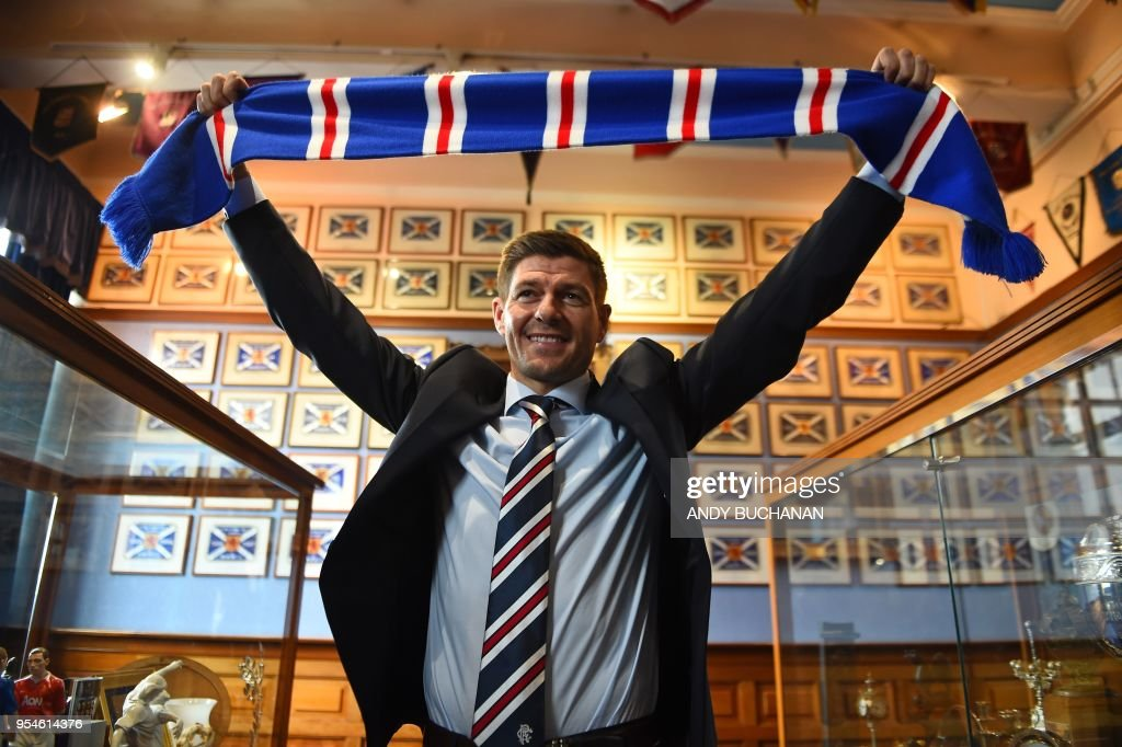 TOPSHOT - Former England and Liverpool captain Steven Gerrard smiles as he holds up a Rangers scarf in the trophy room as he is unveiled as Rangers' new manager at Ibrox Stadium in Glasgow, Scotland on May 4, 2018. - Rangers on Friday confirmed former Liverpool and England midfielder Steven Gerrard as their new manager, announcing he would join the Scottish Premiership club this summer on a four-year deal.