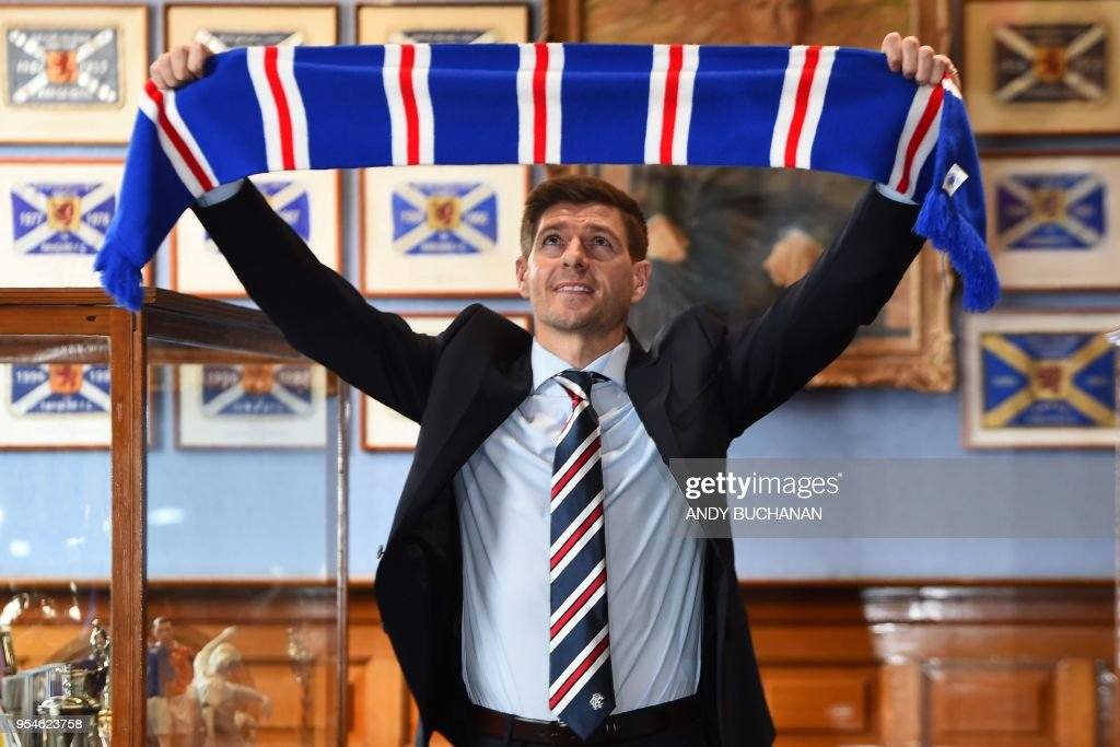 Former England and Liverpool captain Steven Gerrard smiles as he holds up a Rangers scarf in the trophy room as he is unveiled as Rangers' new manager at Ibrox Stadium in Glasgow, Scotland on May 4, 2018. - Rangers on Friday confirmed former Liverpool and England midfielder Steven Gerrard as their new manager, announcing he would join the Scottish Premiership club this summer on a four-year deal.