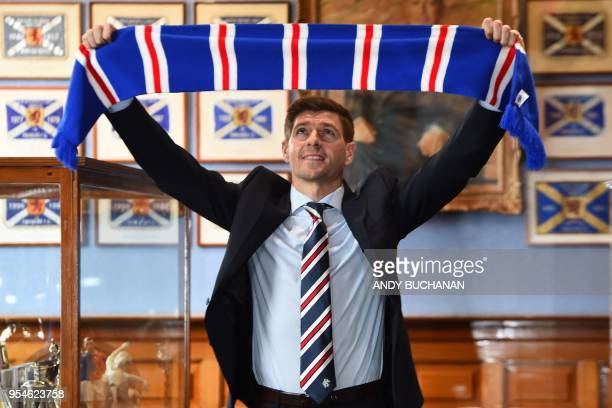 Former England and Liverpool captain Steven Gerrard smiles as he holds up a Rangers scarf in the trophy room as he is unveiled as Rangers' new...