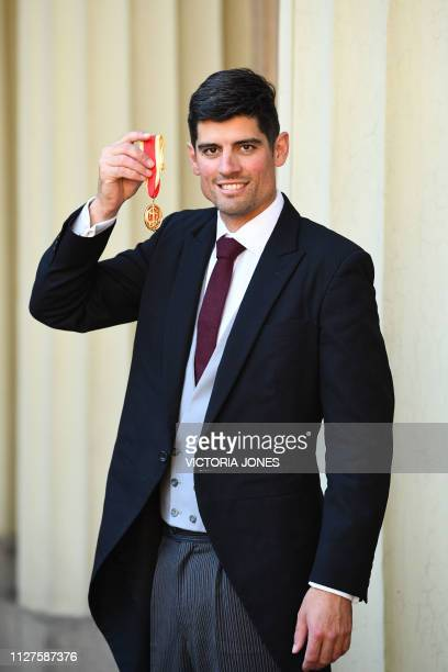 Former England cricket captain Alastair Cook poses with his medal after being appointed as a Knights Bachelor at an investiture ceremony at...