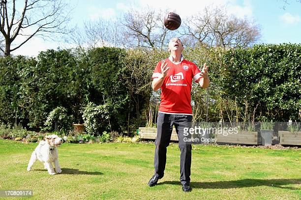 Former England cricketer and television commentator David 'Bumble' Lloyd wearing his Accrington Stanley football shirt plays his dog Tags at his home...
