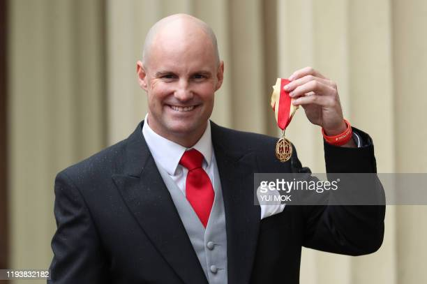 Former England cricketer Andrew Strauss poses with his medal after being knighted as a Knights Bachelor for services to sport following an...