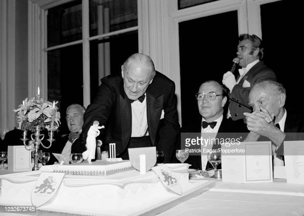 Former England cricketer Gubby Allen inspects the cake during a dinner to celebrate his 80th birthday at Lord's Cricket Ground, London, 9th August...