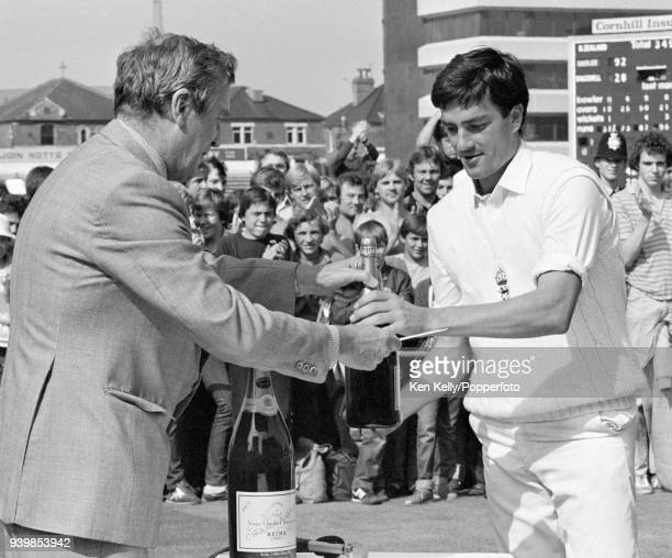 Former England cricketer Jim Laker presents Nick Cook of England with his man of the match award for taking 9 wickets after England won the 4th Test...