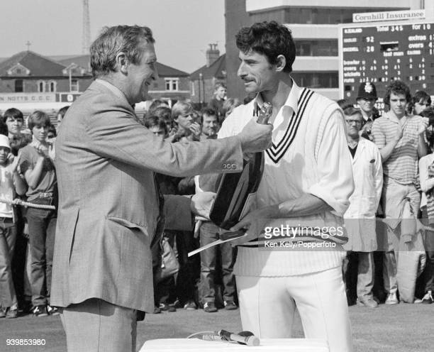 Former England cricketer Jim Laker presents Richard Hadlee of New Zealand with his man of the series award after England won the 4th Test match...