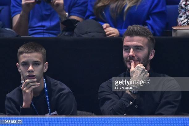 Former England football captain David Beckham and his son Romeo, watch as France's Pierre-Hugues Herbert and France's Nicolas Mahut play against US...