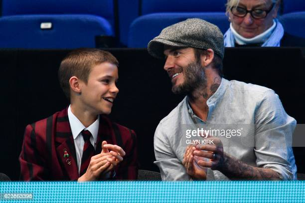Former england footballer David Beckham and his son Romeo applaud while watcing the round robin stage men's doubles match between Brazil's Bruno...