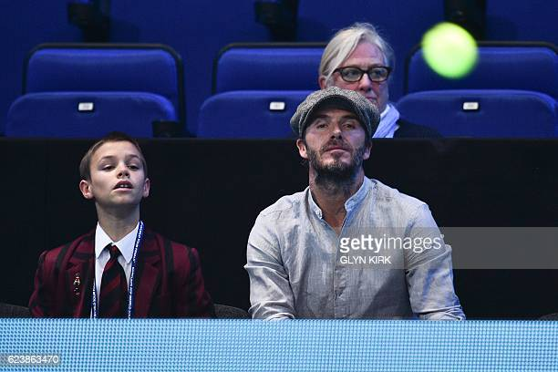 Former england footballer David Beckham and his son Romeo watch the round robin stage men's doubles match between Brazil's Bruno Soares and Britain's...