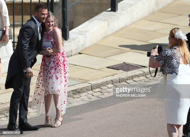 Former England footballer David Beckham poses for a photograph with a young guest as he arrives for the wedding ceremony of Britain's Prince Harry...
