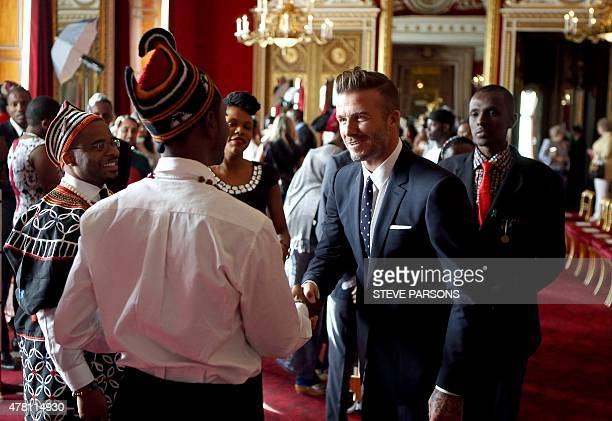 Former England footballer David Beckham talks to guests during a reception for The Queen's Young Leaders from across the Commonwealth at Buckingham...