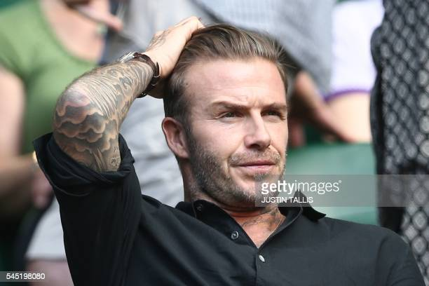Former England footballer David Beckham watches Switzerland's Roger Federer's victory on centre court after he beat Croatia's Marin Cilic in their...
