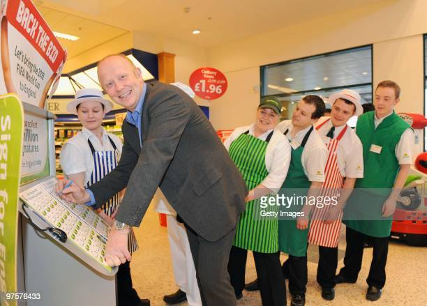 Former England footballer Mark Wright and Morrisons staff members pose during a photo call to promote Morrisons as a sponsor of the England bid to...