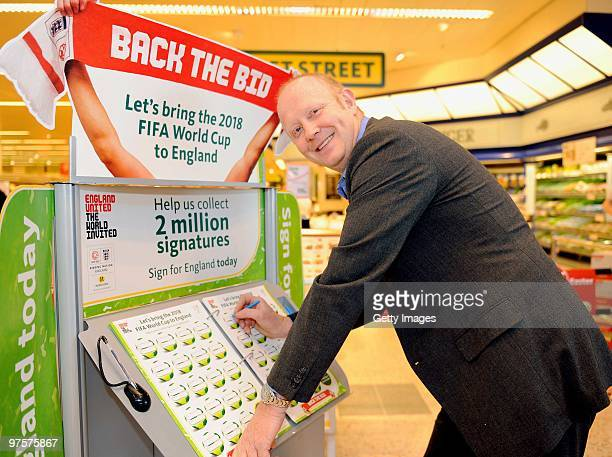 Former England footballer Mark Wright poses as he signs the bid book during a photo call to promote Morrisons as a sponsor of the England bid to host...