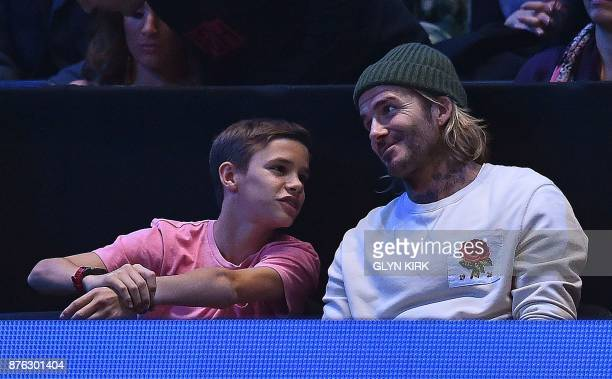 Former England international football player David Beckham and his son Romeo watch as Bulgaria's Grigor Dimitrov returns to Belgium's David Goffin...