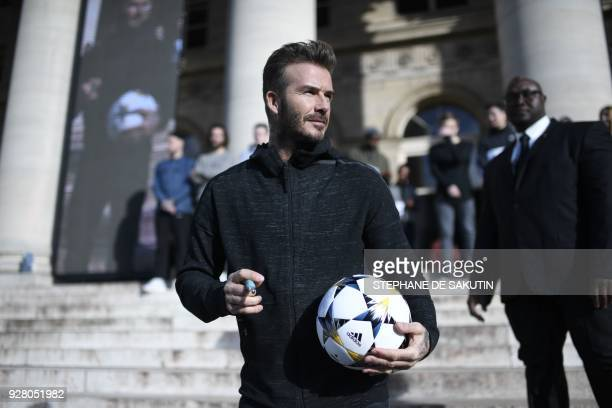 TOPSHOT Former England international football player David Beckham signs a ball outside the palais Brongniart in Paris on March 6 2018 during an...