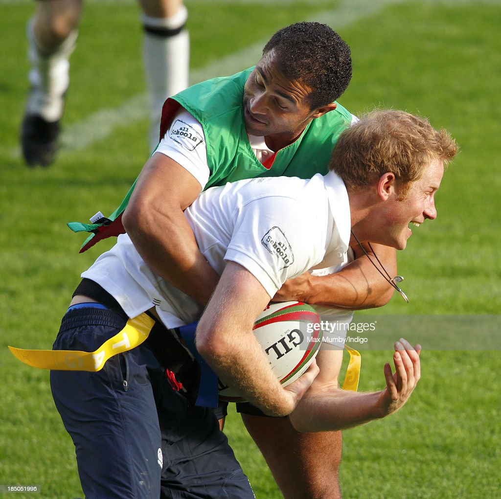 Former England International Jason Robinson and Prince Harry, in his role as Patron of the Rugby Football Union All Schools Programme, tussle as they take part in a rugby coaching session at Twickenham Stadium on October 17, 2013 in London, England.