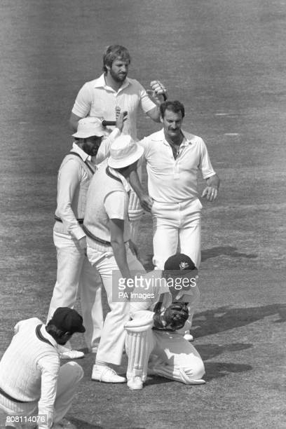 Former England skipper Ian Botham heads off for the pavillion after being caught by Rod Marsh while Dennis Lillee the bowler congratulates Rodney...