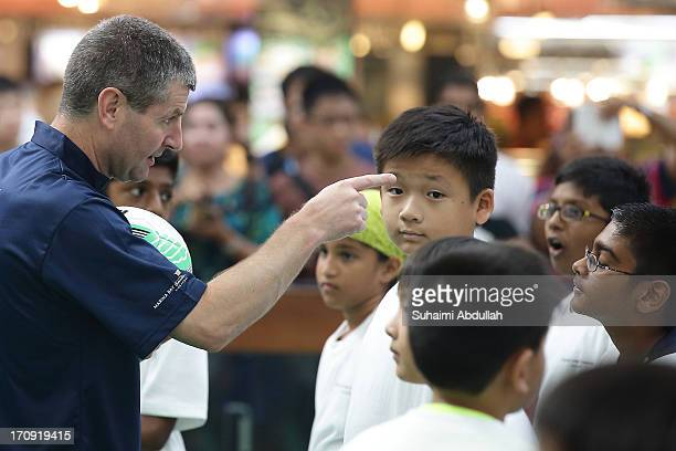 Former English football player Dennis Irwin takes part in a football clinic with students from designated charities and local Singapore schools...