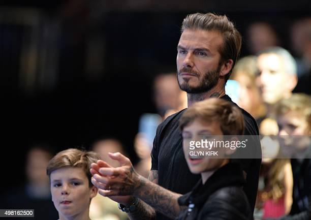Former English footballer David Beckham and his sons Cruz and Romeo watch Spain's Rafael Nadal playing Serbia's Novak Djokovic during the men's...