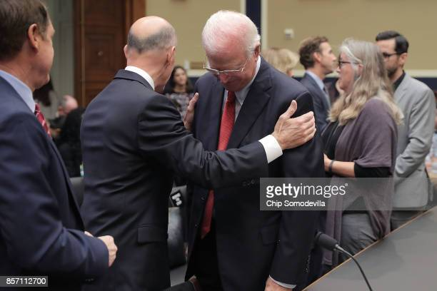 Former Equifax CEO Richard Smith embraces Former Republican Senator from Georgia Saxby Chambliss before Smith testifies to the House Energy and...