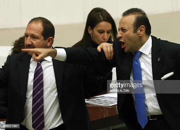 Former European Affairs Minister Egemen Bagis is restrained by colleagues as he argues with opposition lawmakers during a debate on corruption at...