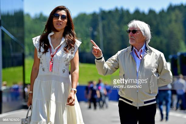 Former F1 boss Bernie Ecclestone and his wife Fabiana Flosi walk in the paddock ahead of the Austrian Formula One Grand Prix in Spielberg, central...