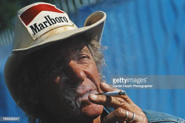 Former F1 Grand Prix and Sportscar driver Arturo Merzario smokes a cigarette whilst wearing his trademark cowboy hat with sponsorship patches from...