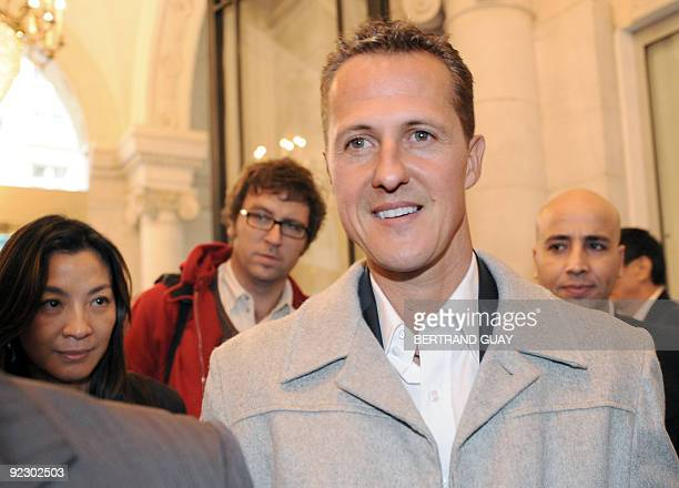 Former F1 world champion German Michael Schumacher flanked by actress Michelle Yeoh companion of exFerrari F1 team chief French Jean Todt leave the...