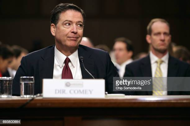 Former FBI Director James Comey immitates a gesture he said he saw President Donald Trump make during one of their conversations while he testifies...