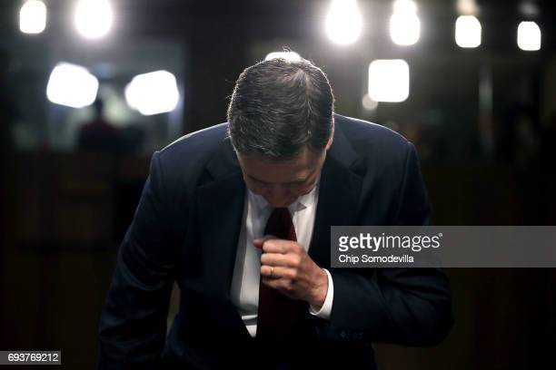 Former FBI Director James Comey takes his seat after being sworn in before the Senate Intelligence Committee in the Hart Senate Office Building on...