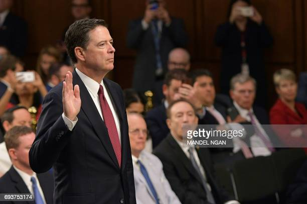 Former FBI Director James Comey takes the oath before he testifies during a US Senate Select Committee on Intelligence hearing on Capitol Hill in...