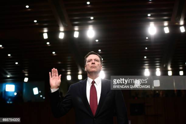 TOPSHOT Former FBI Director James Comey takes the oath before he testifies during a US Senate Select Committee on Intelligence hearing on Capitol...