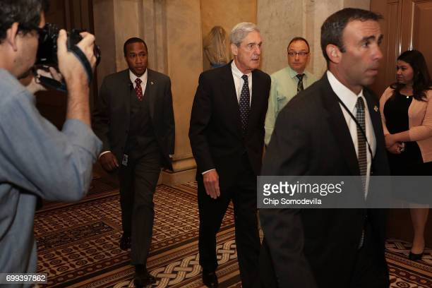 Former FBI Director Robert Mueller is surrounded by security and staff as he leaves a meeting with senators at the US Capitol June 21 2017 in...