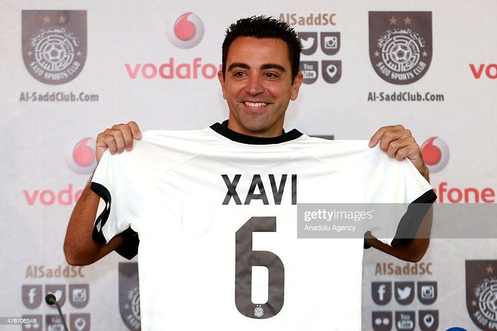 sports shoes 909bb 3e12f Former FC Barcelona player Xavi Hernandez holds his new Al ...