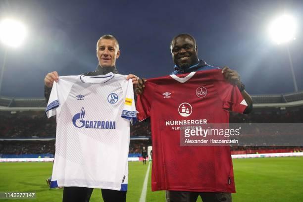 Former FC Nuernberg Marek Mintal and Former FC Shalke 04 player Gerald Asamoah exchange team jerseys prior to the Bundesliga match between 1. FC...