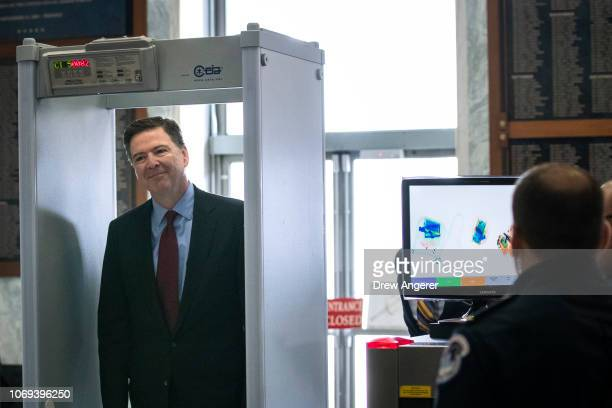 Former Federal Bureau of Investigation Director James Comey goes through security as he arrives at the Rayburn House Office Building before...