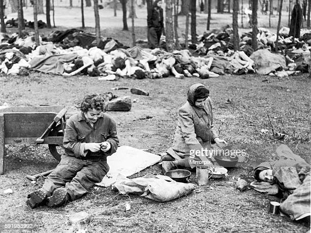 Former female prisoners of Bergen Belsen concentration camp peeling potatoes in front of piles of dead bodies in the camp after it was liberated by...