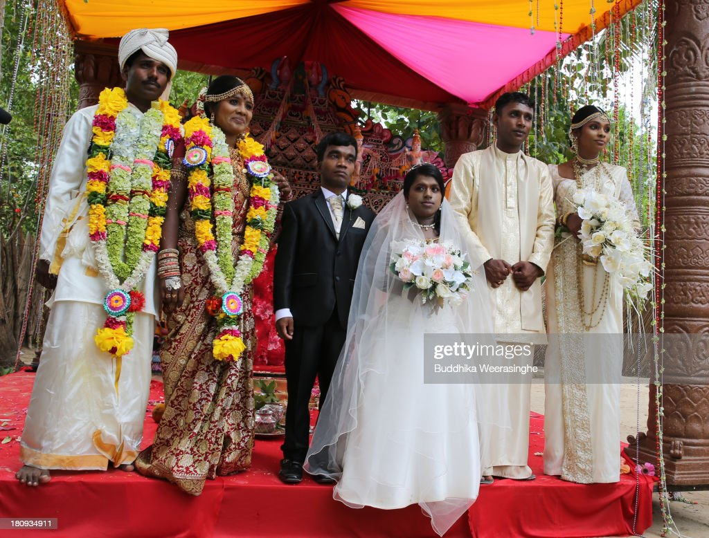 Former female Tamil rebel, Premarathnam Suganthini (R), 19 years old, and her groom H.N. Rathnayaka, 23 years old, attend a group photograph with another two rebel couples during the wedding ceremony at the Civil Defence Force military camp on September 18, 2013 in Vishwamadu, Sri Lanka. The former female Tamil rebel and a Sinhalese military officer were legally married today in Sri Lanka's war-torn Northern province. Sri Lanka suffered through a 26-year civil war between the Tamil Tigers and the Sri Lankan military which ended in 2009. On September 21 Sri Lankans of the Northern Province will head to the polls for provincial council elections for the first time since the conflict began.