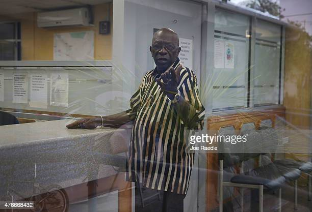 Former Fifa vicepresident Jack Warner reacts to being photographed as he waits to sign in at the front desk of the Arouca Police Station as required...