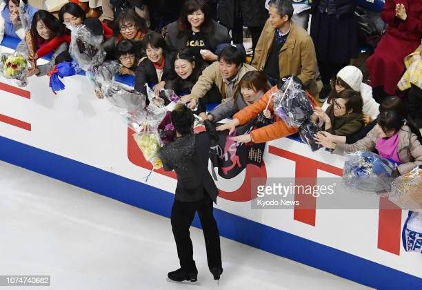 Former figure skating world champion and men's Vancouver Olympic bronze medalist Daisuke Takahashi receives flowers from fans after his free program...
