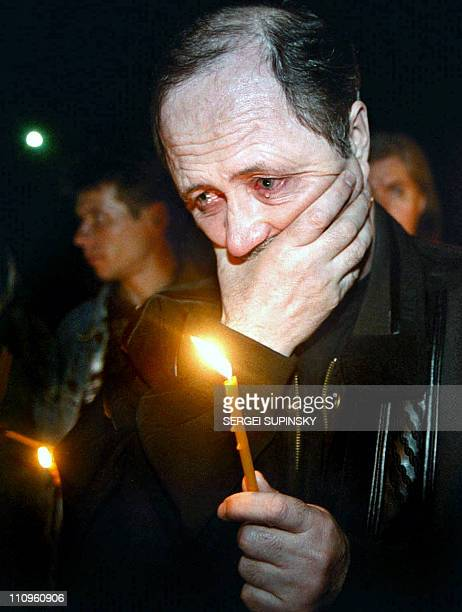 A former fireman with a candle in his hand cries for dead friends at the Memorial of the Perished Firemen in Kiev 26 April during a memorial ceremony...