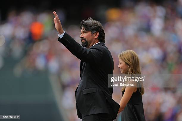 Former first baseman Todd Helton of the Colorado Rockies waves to the crowd as he walks onto the field with his daughter Tierney Faith Helton during...