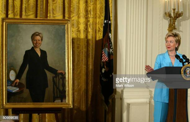 Former first lady and US Senator Hillary Clinton speaks while standing near her portrait during a ceremony to unveil Clinton portraits in the East...