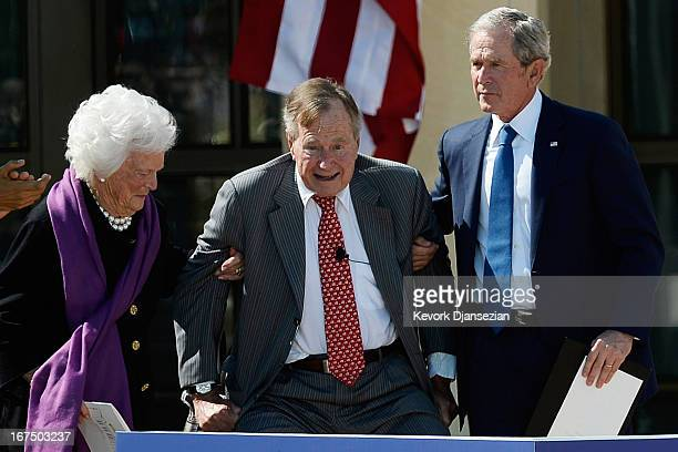 Former first lady Barbara Bush and former President George W Bush help up former President George HW Bush during the opening ceremony of the George W...