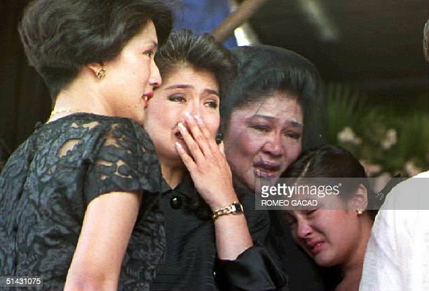 Former first lady Imelda Marcos and her children Irene Araneta Imee Manotoc and adopted daughter Aimee weep 09 September 1993 during a public eulogy...