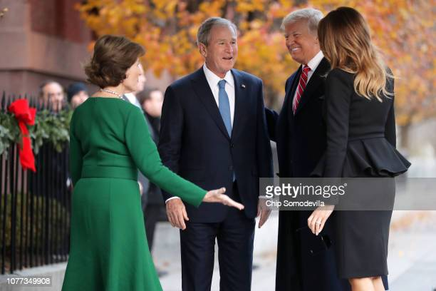 Former first lady Laura Bush and former President George W Bush greet President Donald Trump and first lady Melania Trump outside of Blair House...