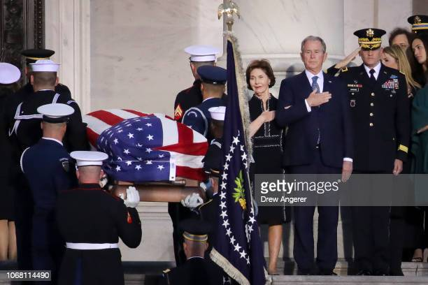 Former first lady Laura Bush and former president George W Bush look on as the casket of the late former President George HW Bush arrives at the US...