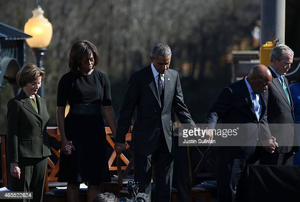 Former first lady Laura Bush first lady Michelle Obama US president Barack Obama US Rep John Lewis and former US president George W Bush pray during...